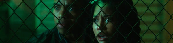 The First Purge characters behind a fence watching horror