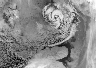 An Arctic hurricane (or polar low) northeast of Scandinavia, with a characteristic eye and counter-clockwise swirl of clouds. They grey area in the upper left-hand corner is sea ice.