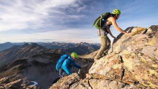 Two people scrambling up rocks