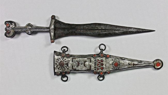 The restored dagger and sheath. Both are decorated with red glass.