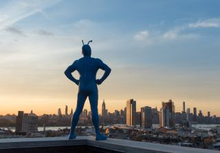 A still taken from the Amazon TV show The Tick or Tick standing on a building