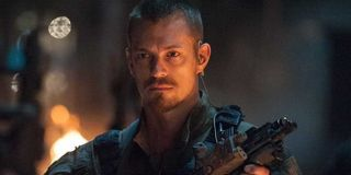 Rick Flag (Joel Kinnaman) holds a gun and stands in front of a fire in 'Suicide Squad'