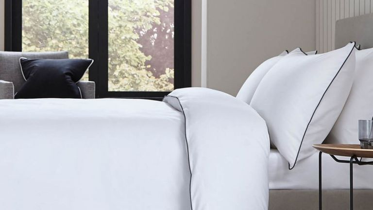 A white duvet cover and pillow cases with black piping on a bed in a contemporary bedroom