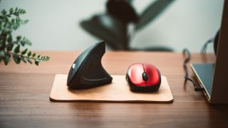 Ergonomic mouse and normal computer mouse. Black vertical optical computer mouse with ergonomic design, designed to reduce injuries such as carpal tunnel syndrome, arthritis.