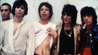 The Rolling Stones standing against a wall, Mick Jagger pulling his t-shirt up.