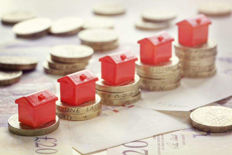buy to let mortgages: Small red houses balanced on top of pound coins