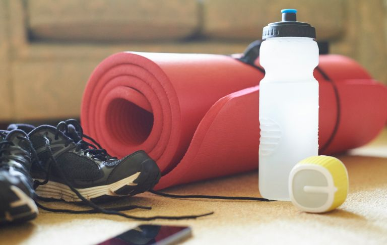 Yoga mat, water bottle and running shoes