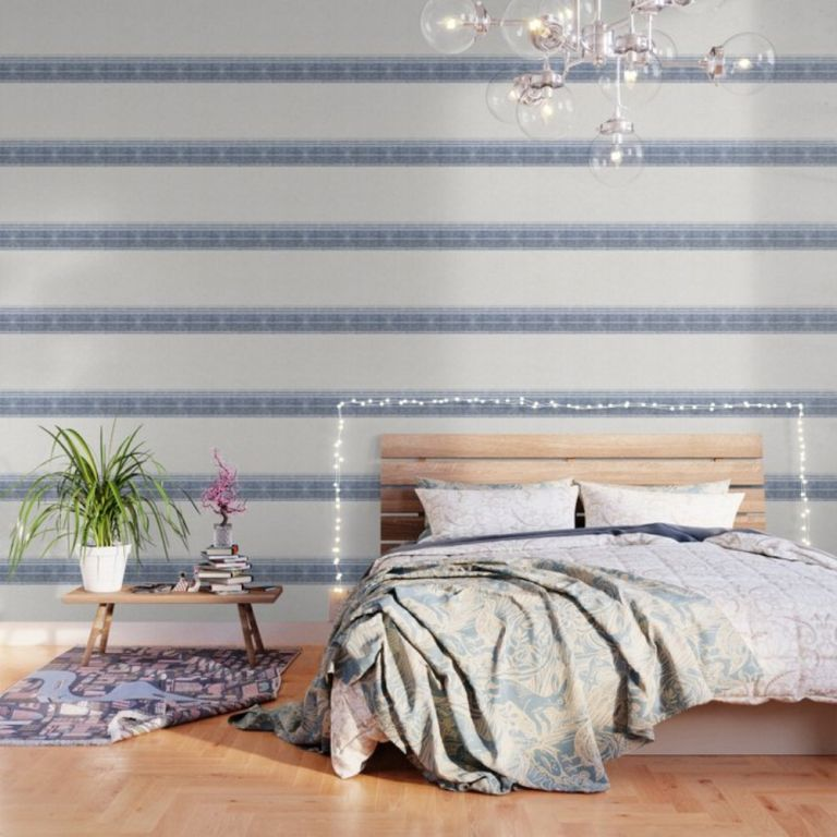 striped blue and white wallpaper in etherial sleeping space with wooden headboard