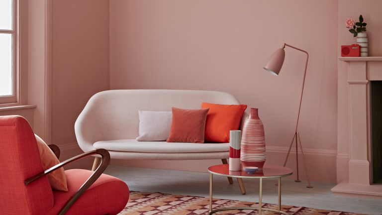 blush pink living room with sofa and little armchair by crown
