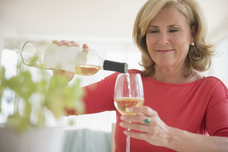 a woman in a red shirt pours a glass of white wine
