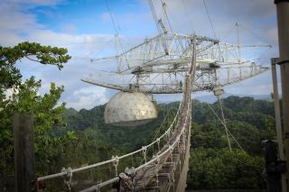 An image of Arecibo Observatory's iconic radio telescope before damage that began in August 2020; the curved azimuth arm and the dome suspended from it are both visible.