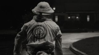 A black and white still of a beekeeper standing in a street wearing a SWORD logo on his back