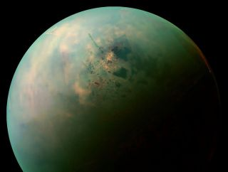 A false-color view of Titan taken by the Cassini spacecraft. The orange spots may be solids left behind when a liquid hydrocarbon seas evaporated, similar to what happens in a bathtub when it is drained.