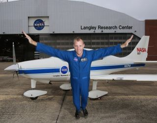 NASA research pilot Greg Slover spreads his arms like wings at the Langley Research Center to celebrate National Aviation Day.