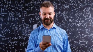 Smiling, bearded teacher looks at cell phone while standing in front of blackboard covered with chemistry equations
