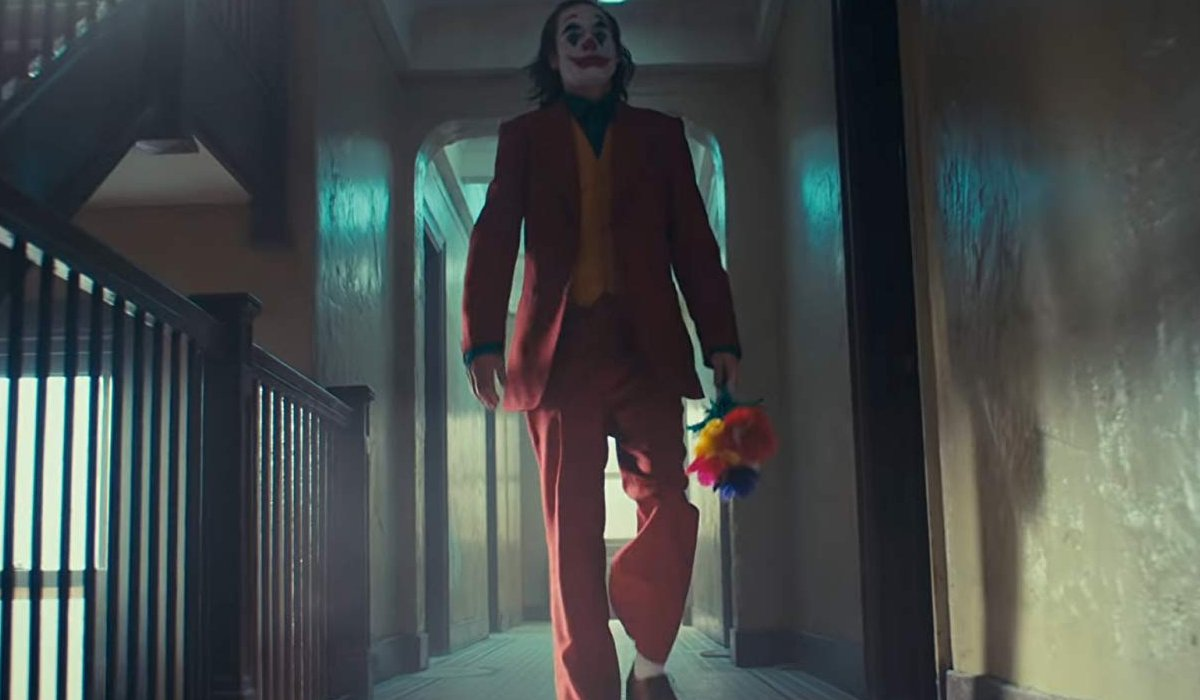 Joker walks down the hallway with fake flowers in hand