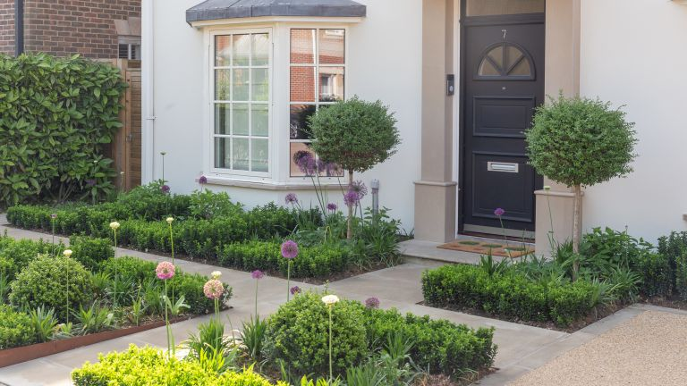 landscaping ideas for front of house: modern garden with formal paths and flowerbeds