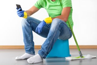 Man sitting in kitchen with mop.