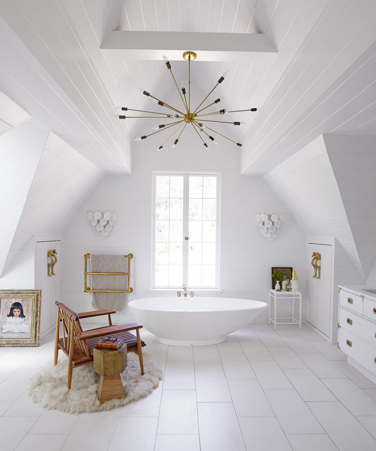 An example of bathroom ceiling lighting ideas showing a large white bathroom with a freestanding bath, a wooden chair and a sputnik light