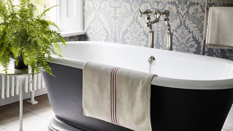 Wallpapered bathroom with black rolltop by Little Greene