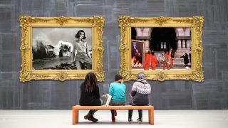 Three people sitting in an art gallery looking at Rush artwork