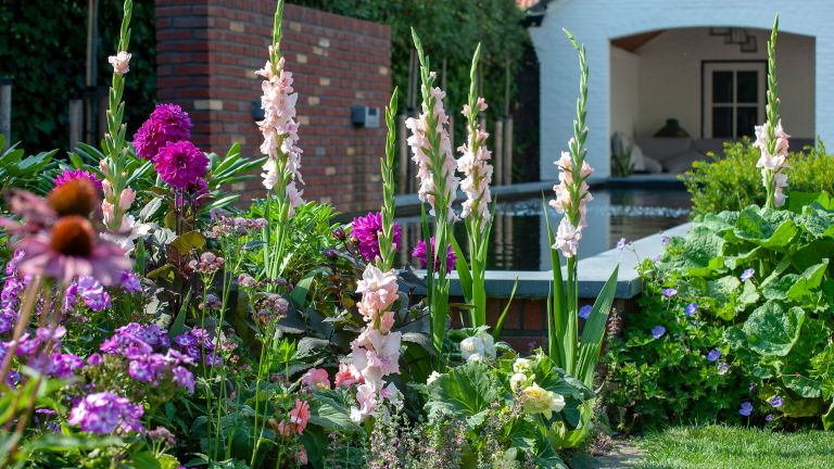 flowerbed ideas: purple flowers in front of water feature