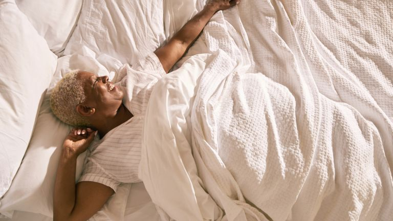 woman stretching in bed with white blanket
