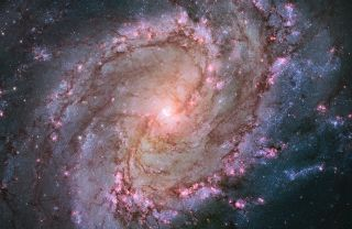This Hubble Space Telescope image shows the full beauty of nearby spiral galaxy M83 in a mosaic of many photos stitched together. The magentas and blues indicate star-forming regions. Also known as the Southern Pinwheel, M83 is located 15 million light-ye