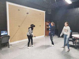 Three students sharing VR gear