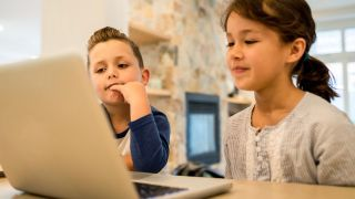 Young brother and sister use a laptop in the kitchen