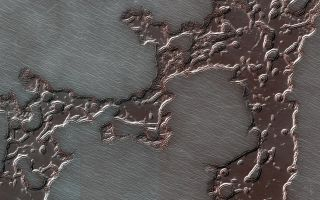 Upper layers of frozen carbon dioxide have melted to show layers of frozen water ice at the South Pole of Mars in this image taken by NASA's Mars Reconnaissance Orbiter.