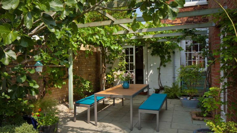 pergola with dining table in a back garden