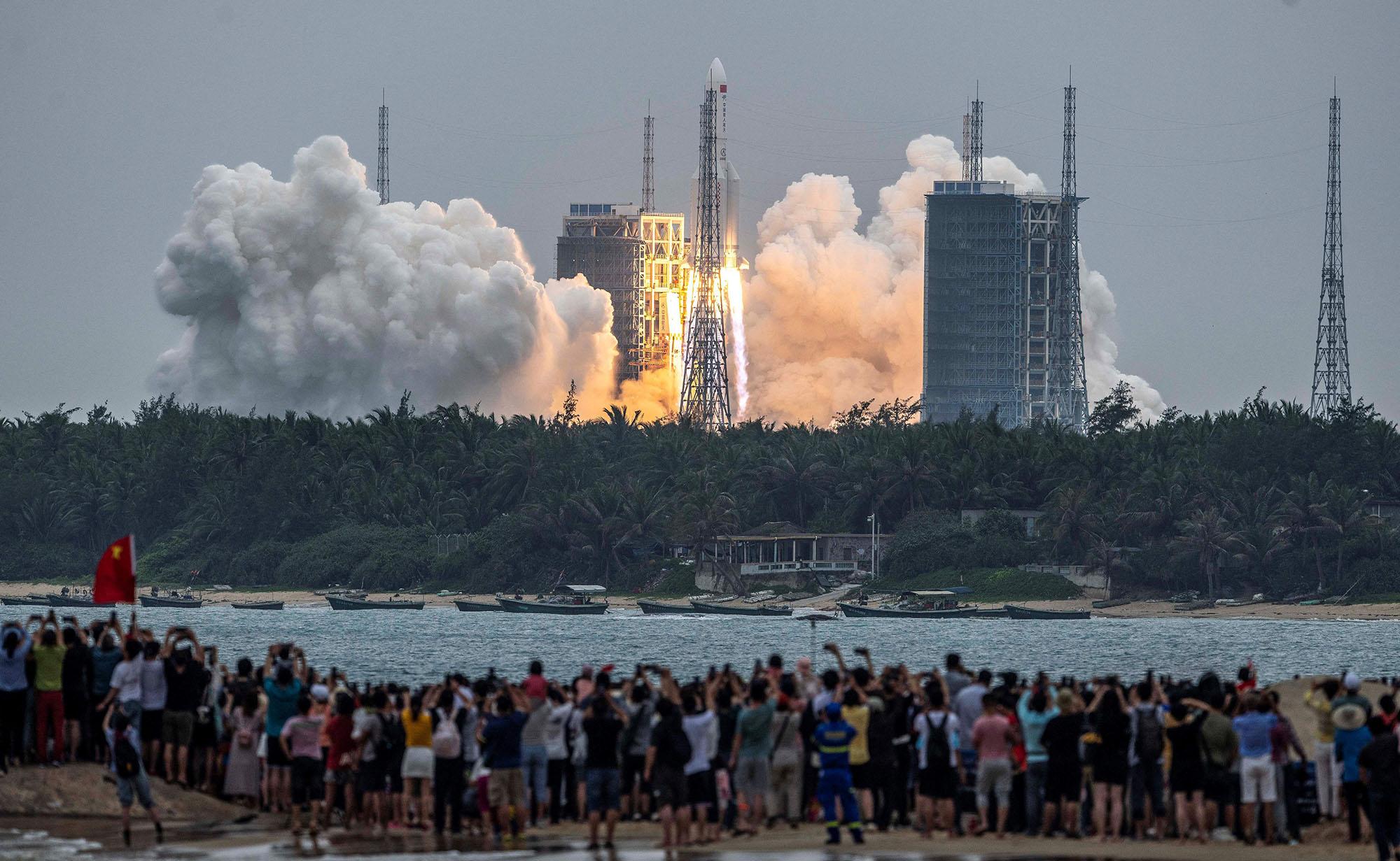 يشاهد الناس صاروخ Long March 5B ، الذي يحمل الوحدة الأساسية لمحطة Tianhe الفضائية الصينية ، وهو ينطلق من مركز Wenchang للإطلاق الفضائي في مقاطعة هاينان جنوب الصين في 29 أبريل 2021 (مصدر الصورة: STR / AFP / Getty)