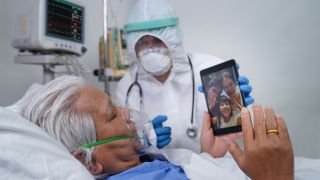 COVID-19 patient in hospital bed on video call with family