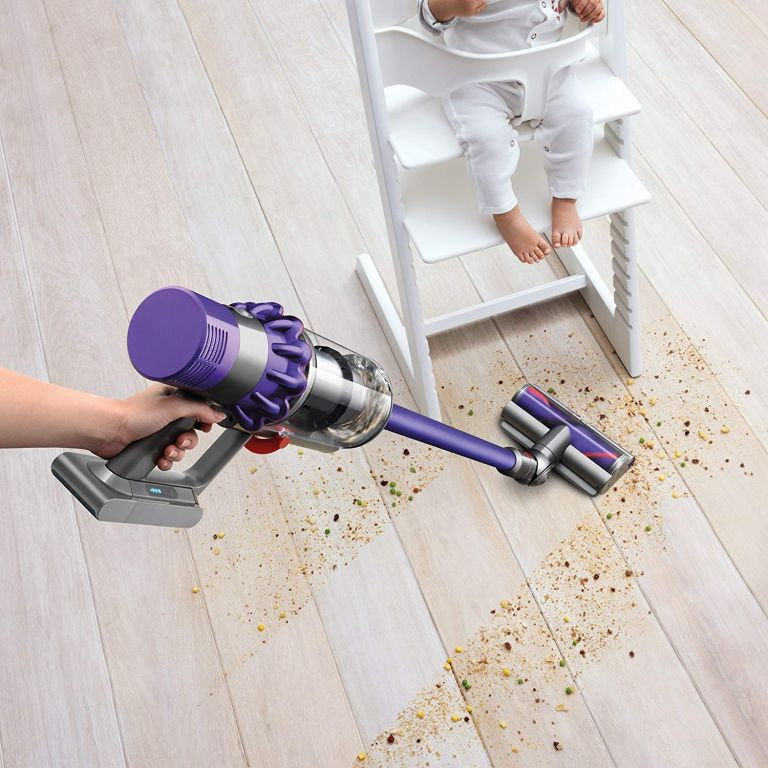 Which cordless vacuum cleaner? Dyson cordless vacuum vacuuming crumbs on floor near high chair