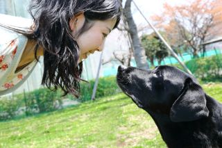woman gazing into black lab's eyes