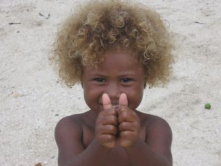 A blond-haired Solomon Island child smiles for the camera