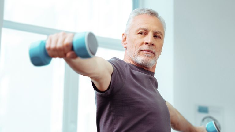 Older man lifting weights to help lose weight and increase metabolism