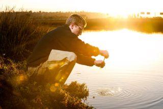 David Cummings taking samples of urban storm water