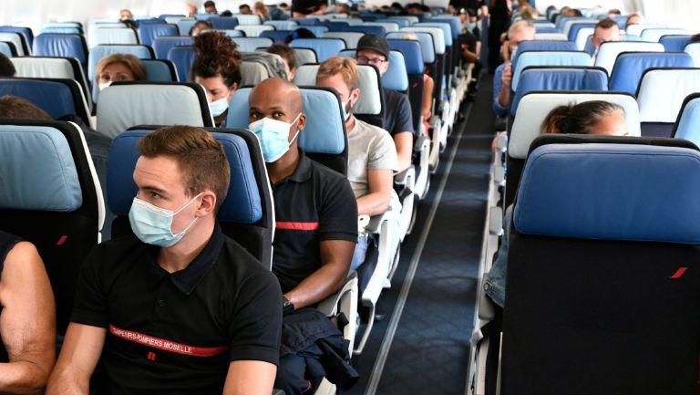 Volunteer medical workers and firemen sit in their plane with masks prior to flying to French overseas department of Martinique and Guadeloupe amid the Covid-19 pandemic, at the Orly airport in Orly, near Paris, on August 20, 2021.