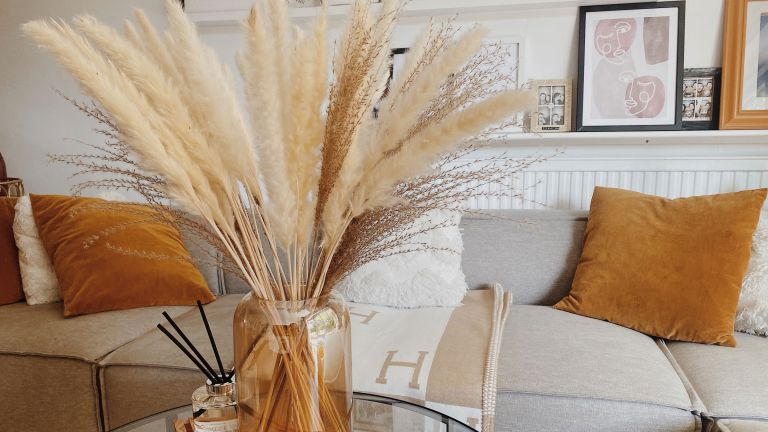 Dried pampas grass on coffee table with grey sofa behind