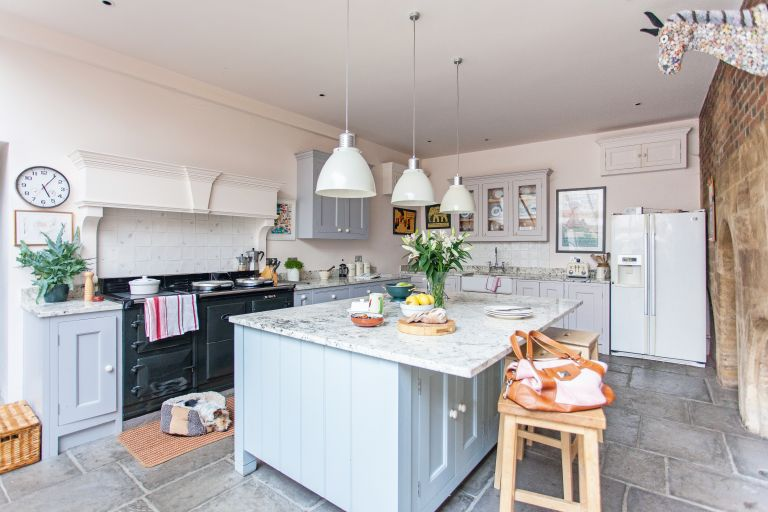 interior of kitchen in grade i listed tudor home with grey cabinets and aga