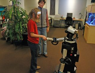 A child interacting with Robovie, a remotely controlled humanoid robot.