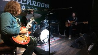 JD Simo performing from a stool in Sheffield on April 6