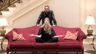 Mantra Vega's Heather Findlay and Dave Kerzner throwing yoga poses on a red sofa