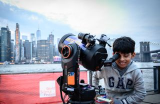 "A child uses a telescope at the ""Saturday Night Lights"" event held at Brooklyn Bridge Park as part of the 2019 World Science Festival."