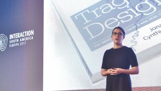 Generate speaker Cynthia Savard Saucier on stage with her book, Tragic Design, in the background
