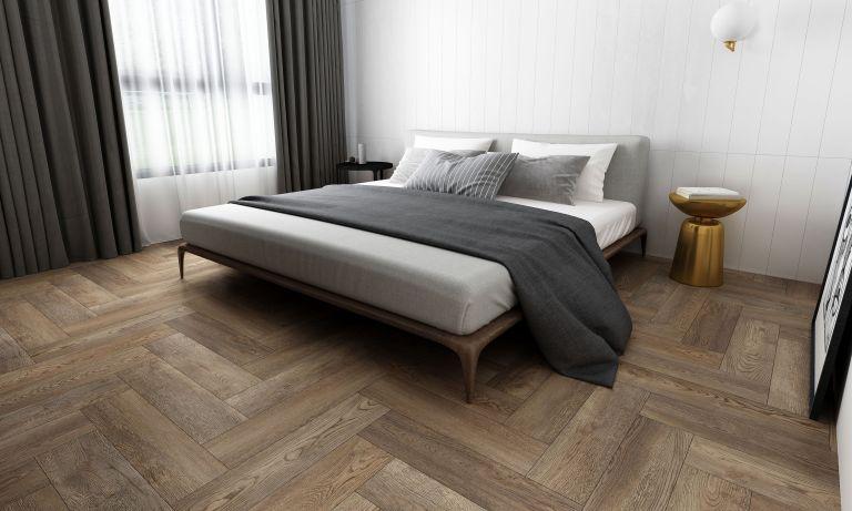 Gray LVT flooring in herringbone wood imitation design in modern bedroom with gray bedding