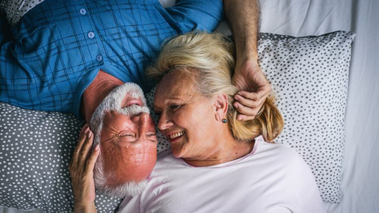 older couple in bed together in bed