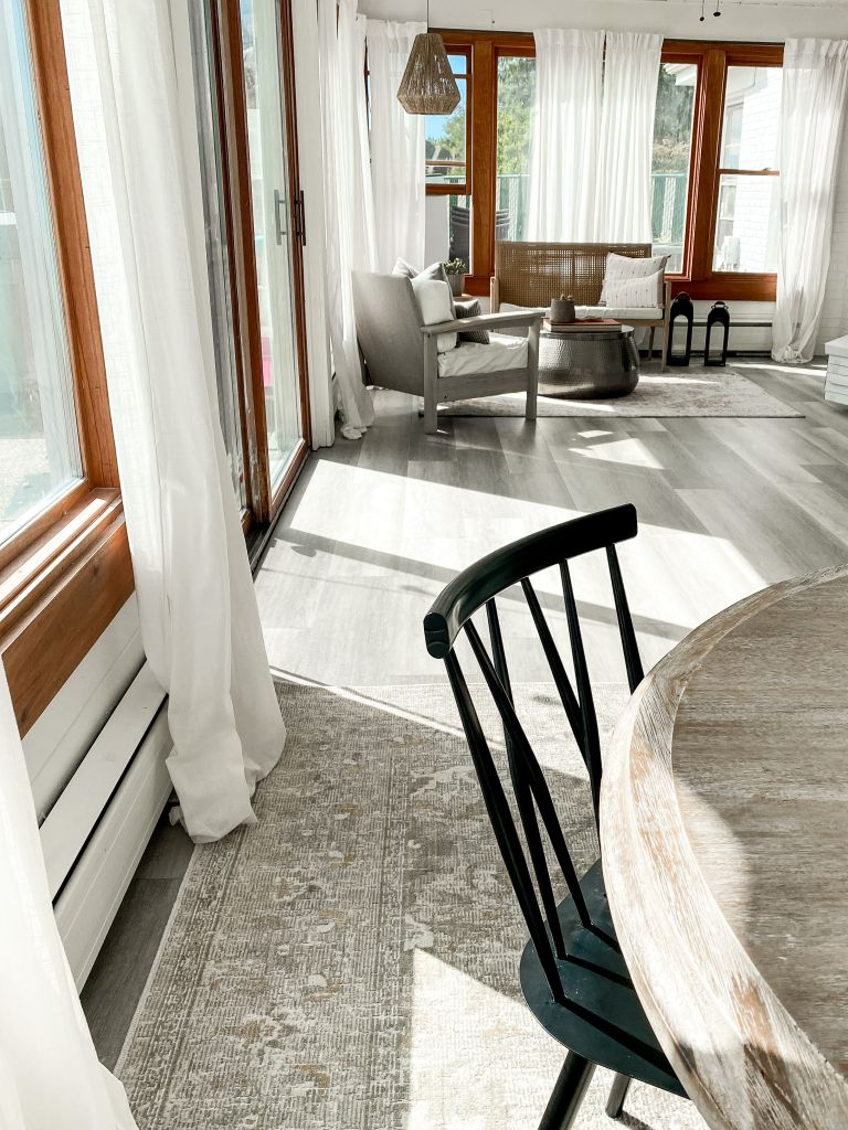 Grey laminate floor in sunroom with round dining room table and wooden chair